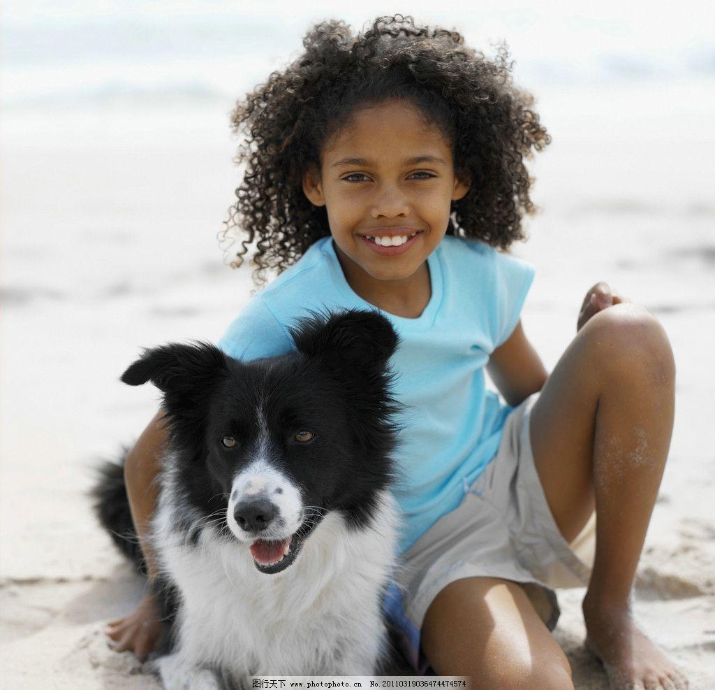 沙滩抱着小狗的小女孩图片